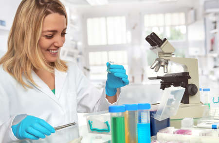 Female scientist in lab coat and protective gloves ilaughts while looking at glass vial. Work in progress in scientific laboratory.