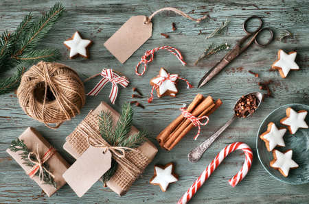Hand crafted gifts on dark rustic wooden table with Christmas decorations. Seasonal background shot from above. Flat lay, top view, filtered image. Tag mockup, copy space on the tags. Stock Photo