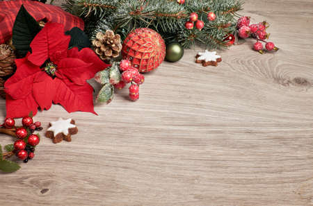 Wooden background with poinsettia, or Christmas Star, decorated Christmas tree twigs and baubles, text space