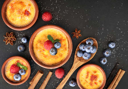 Creme brulee (cream brulee, burnt cream) with raspberry, blueberry and mint in terracota clay baking dishes. Top view, dark stone background. 版權商用圖片