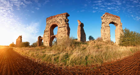 Ruins of the ancient aqueduct on Appia Way near Villa Quintili in Rome, Italy in Fall. Panoramic image.