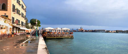 Seaside restaurant on Fondamenta Zattere overlooking lagoon in Southern Venice, Italy, panoramic image Stock Photo