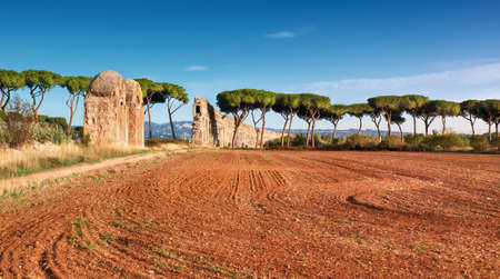 Ruins of the ancient aqueduct on Appia Way near Villa Quintili in Rome, Italy. Panoramic image. Stock Photo