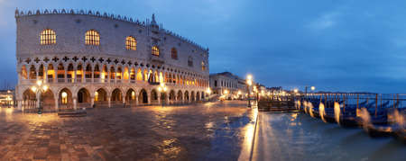Panoramic view of Doges Palace, or Doge Palace and gondolas on a rainy night in Venice, Italy