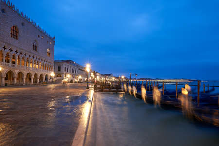 Doges Palace, or Doge Palace, and moored gondolas dancing on waves on a rainy night in Venice, Italy