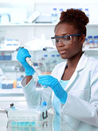 Cientista afro-americano ou estudante de pós-graduação em jaleco e vestuário de proteção funciona em laboratório moderno Foto de archivo