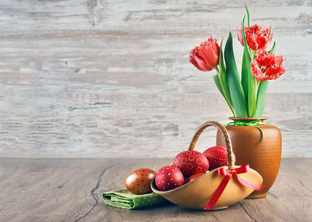 Red tulips and painted Easter eggs on wooden background, space for your text