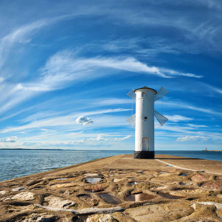 Old lighthouse in Swinoujscie, a port in Poland on the Baltic Sea. The lighthouse was designed as a traditional windmill. Panoramic square image.