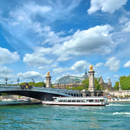 Paris, France, passenger boat passes under Alexander III bridge on Seine river in Spring. Panoramic image, square composition.