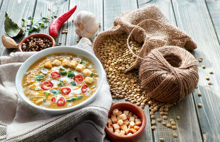 Spicy lentil soup with chili, garlic and onion on rustic wooden table. The soup is served with cream, chili, lemon, croutons and thyme leaves in white bowl, with ingredients all around. Stock Photo