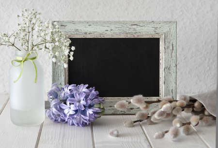 Spring flowers around a blackboard in rustic frame: hyacinth, pussy-willow and Babys Breath. Space for your text.