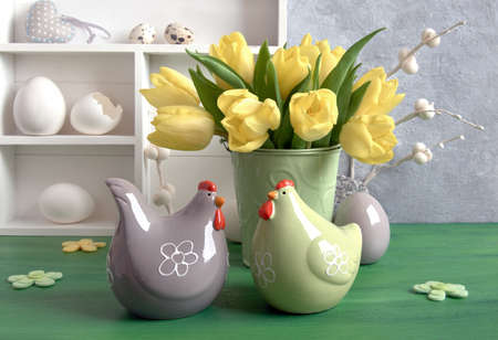 Easter composition with yellow tulips, felt flowers, ceramic hens and Easter eggs