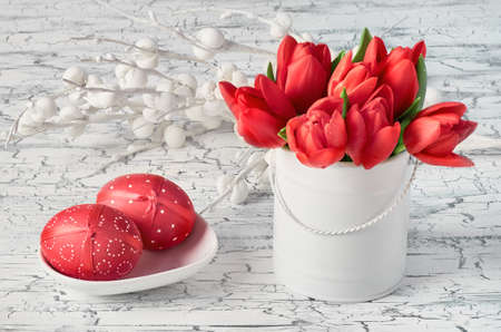 Bunch of red tulips and two red Easter eggs on white cracked background 스톡 콘텐츠