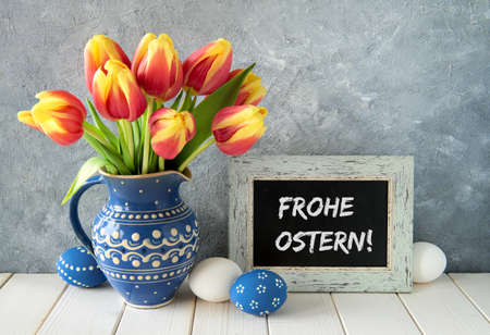 Red-yellow tulips in blue ceramic pitcher with Easter eggs and a blackboard on gray background. Text