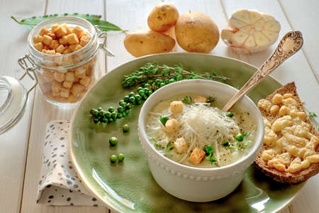 Homemade cream of potato soup with croutons and parmesan cheese, served with bread toasted with cheese on light wooden table