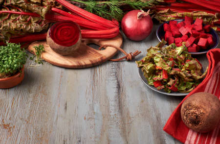 Food background with red beet root and beet leaves, whole and cut, and space for your text