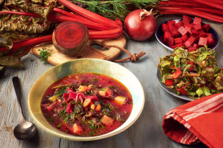 Spring food background with red beet vegetable soup. Ingredients: red beet root, fresh beet leaves, potatoes and carrots, served with dill.