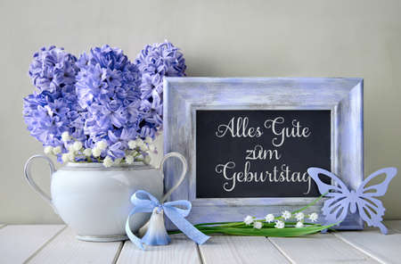 Blue decorations and hyacinth flowers on white table, blackboard with text. Springtime Alles gute zum geburtstag postcard design in blue. The text means Happy Birthday in English.  Stock Photo