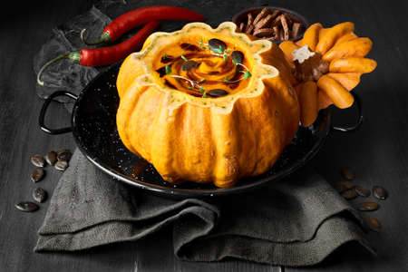 Spicy pumpkin soup served in a hollowed pumpkin on dark wood and stone