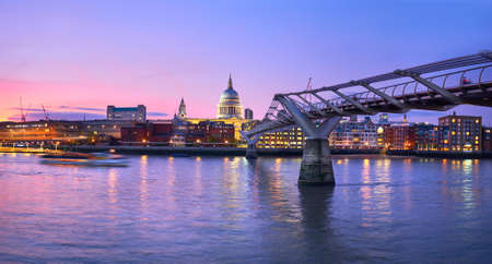 London at sunset, Millennium bridge leading towards illuminated St. Paul cathedral over Thames river with city bathing in electric light. Panoramic toned image. 免版税图像