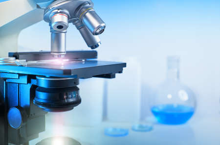 Scientific background with closeup on light microscope and laboratory out of focus. This image is toned Stock Photo