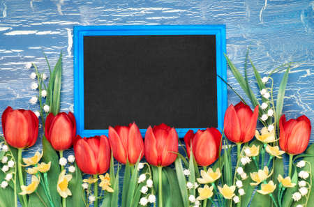 Blackboard with red tulips and lily of the valley flowers on blue rustic background. Space for your test, flat lay, toned image. Stock Photo