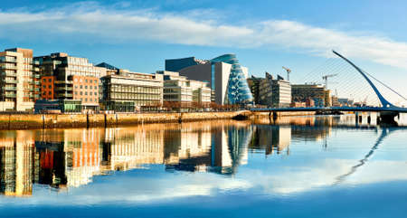 Modern buildings and offices on Liffey river in Dublin on a bright sunny day, with Harp bridge on the right