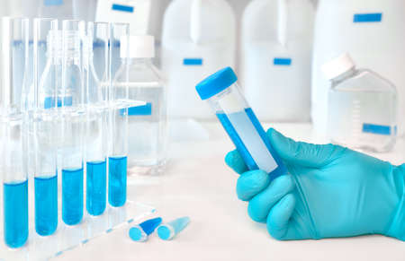 Scientific background in white and blue. Liquid sample in gloved female hand, blue liquid samples in glass and plastic tubes Stock Photo