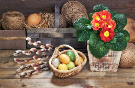 Basket of Easter eggs, red primrose flowers in flower pot and bunch of pussy-villow on wooden table with rustic Spring decorations