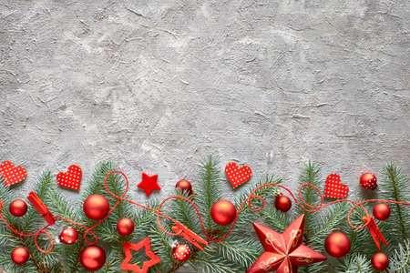 Green and red Cristmas background with fir twigs, hearts and Christmas trinkets on concrete stone background, text space Stock Photo