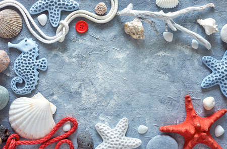 Frame made of sea shells, stones, rope and star fish on blue textured background, text space