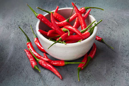Closeup on red hot chili peppers in ceramic bowl over dark textured table. Food background.