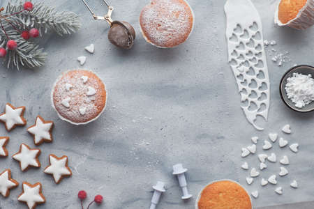 Top view of the table with sugar-sprinkled muffins, fondant icing and Christmas star cookies on light blue background 版權商用圖片
