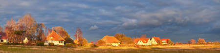 Hiddensee island in the Baltic sea in North Germany. Panoramic image with traditional houses on a sunset. Standard-Bild