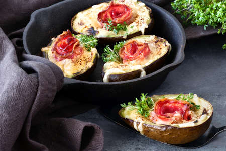 Keto diet dish: Avocado Boats with crunchy bacon, melted cheese and cress sprouts on dark background