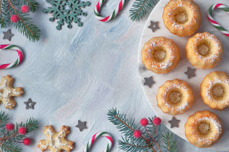 Mini bundt ring cakes with icing sugar on light background with fir twigs, berries and candy canes. Christmas holiday sweet food, flat lay with text space. Stockfoto