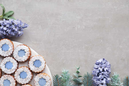 Flower Linzer cookies with blue glazing on light concrete decorated with blue hyacinth flowers, fir twigs and herbs. Top view with copy-space 免版税图像