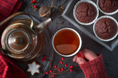 Xmas background with female hand holding hot cup of tea. Flat layout with chocolate muffins, cookies, tea pot and winter decorations on dark gray rustic backgrond.