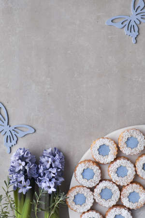 Flower Linzer cookies with blue glazing on light concrete background decorated with blue hyacinth flowers and butterflies. Top view with copy-space.