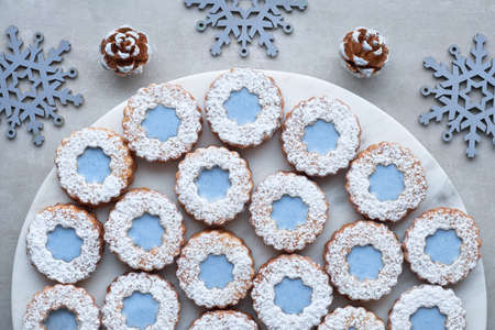 White and blue flower Linzer cookies on light stone background decorated with blue snowflakes pine cones