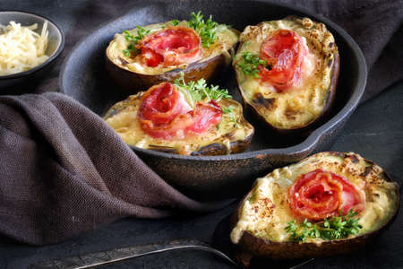 Keto diet dish: Avocado Boats with crunchy bacon, melted cheese and cress sprouts on dark background Stockfoto