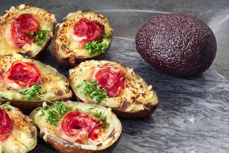 Keto diet dish: Avocado boats with crunchy bacon, melted cheese and cress sprouts on gray stone serving board Imagens - 121840388