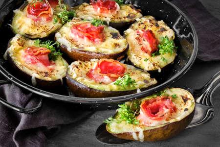 Keto-Diätgericht: Avocado-Boote mit knusprigem Speck, geschmolzenem Käse und Kressesprossen auf dunklem Hintergrund