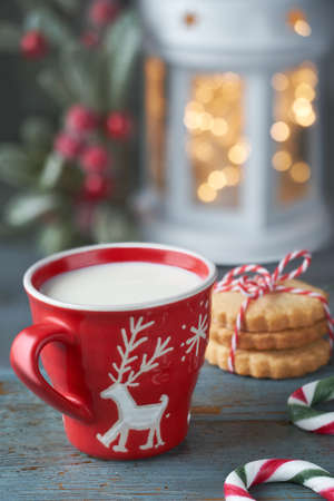 Closeup on red cup of milk with Christmas deer design, cookies, Xmas lights in lantern and berry decorations