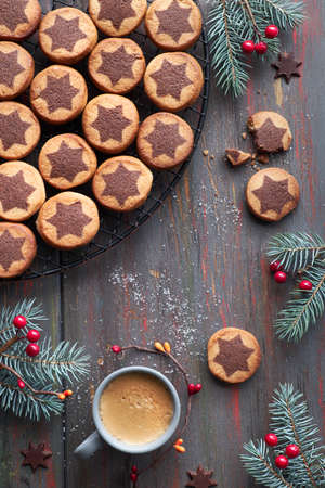 Christmas cookies with chocolate star pattern on cooling rack with spices and decorated fir twigs. Flat lay on dark dark brown textured background.