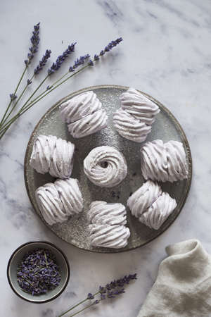 Flat lay with a plate of home-made marshmallows (zephyr, meringue) made with lavender on white marmor stone background