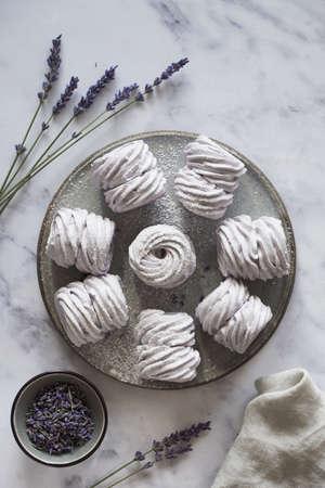 Piatto disteso con un piatto di marshmallow fatti in casa (zephyr, meringa) a base di lavanda su sfondo di pietra marmorizzata bianca Archivio Fotografico