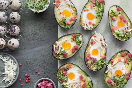 Keto-Diät-Gericht: Avocado-Boote mit Schinkenwürfeln, Wachteleiern, Käse und Kressesprossen auf einem Servierbrett aus Stein stone Standard-Bild