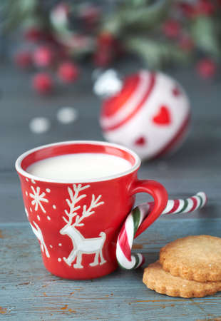 Closeup on red cup of milk with Christmas deer design, cookies on dark rustic wooden table with Xmas berry decorations Stock Photo