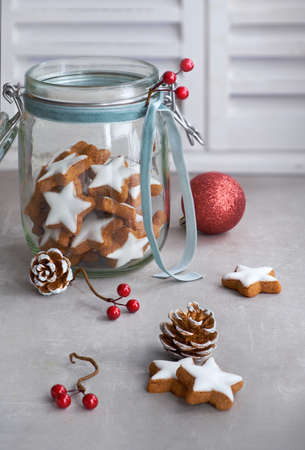 Christmas background with tasty star ginger cookies in a glass jar with winter decorations